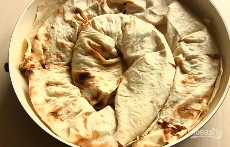 6. Форму для выпечки смажьте растительным маслом и выложите в нее рулеты. Сверху залейте заливкой и выпекайте при 200 градусах 20 минут.