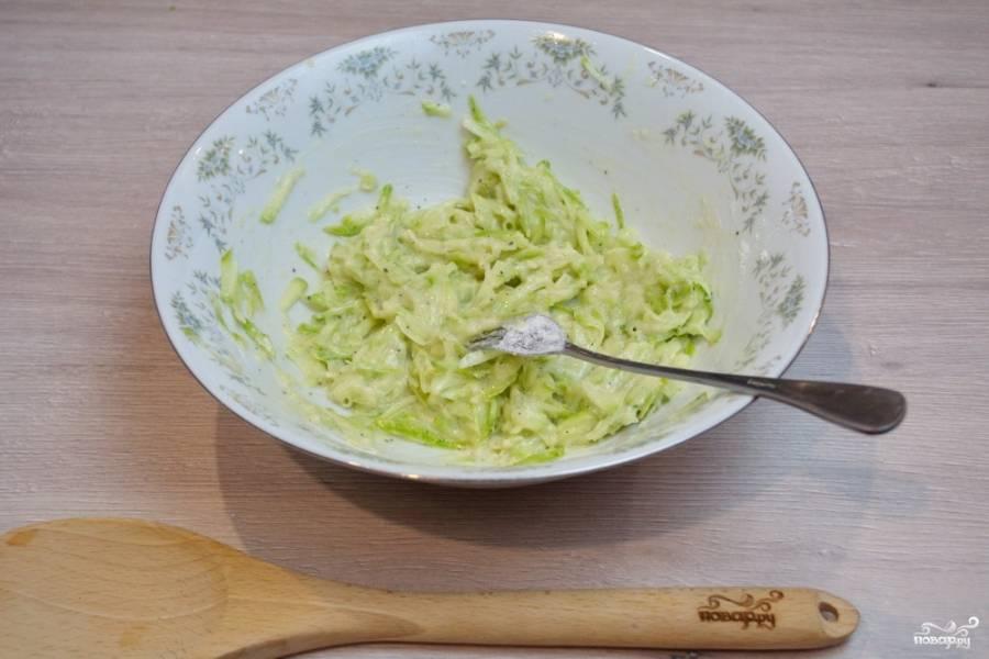 К кабачкам добавьте 2 столовые ложки пшеничной муки. Перемешайте. Добавьте немного соли и черного молотого перца.