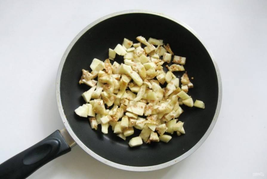 Приготовьте начинку. Мякоть баклажана нарежьте кубиками и выложите в сковороду.
