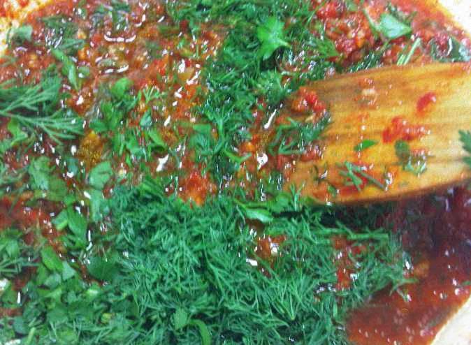 Пока помидоры вскипают, перемалываю перец. Кладу его в кипящие помидоры. Довожу до кипения, добавляю растительное масло и варю около часа на медленном огне. За 10 минут до готовности кладу соль, сахар и уксус. Выключаю. Добавляю молотый чеснок, рубленую зелень. Перемешиваю.