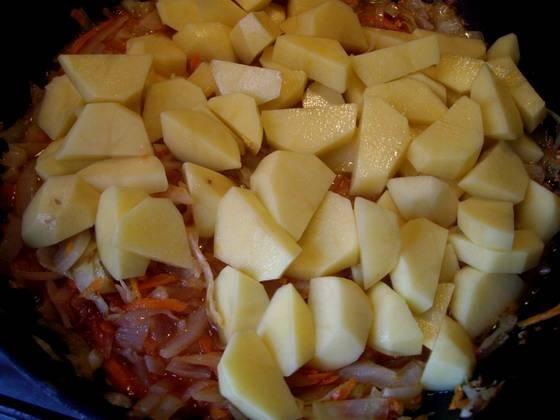 Потом мы добавляем к овощам томатную пасту и нарезанный кубиками картофель, вливаем совсем немного водички и перемешиваем все. Накрываем сковороду крышкой и тушим овощи на медленном огне до полной готовности картофеля.