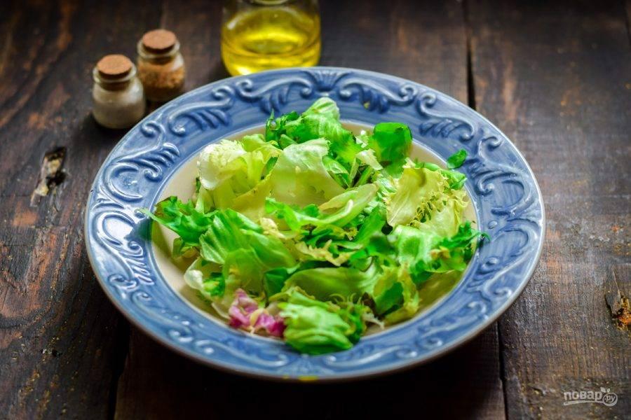 На тарелку выложите салатные листья.