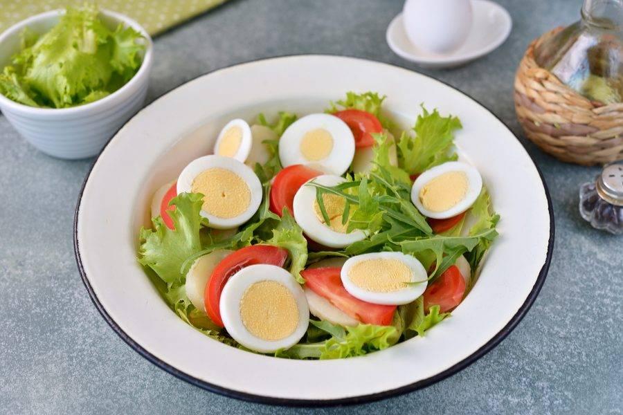 Почистите от скорлупы яйцо, измельчите с помощью яйцерезки, разложите его на ломтики помидора.