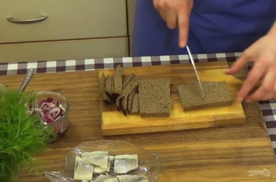 2. Сельдь очистите и нарежьте небольшими кусочками. Ломтики хлеба очистите от корочки и разрежьте на четыре части. Замаринованный лук отожмите и добавьте к нему подсолнечное масло.