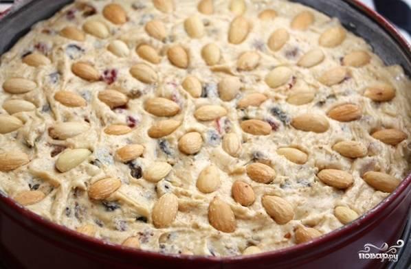 Смажьте форму для выпечки сливочным маслом и немного присыпьте мукой. Влейте тесто, разровняйте и украсьте очищенным миндалём.