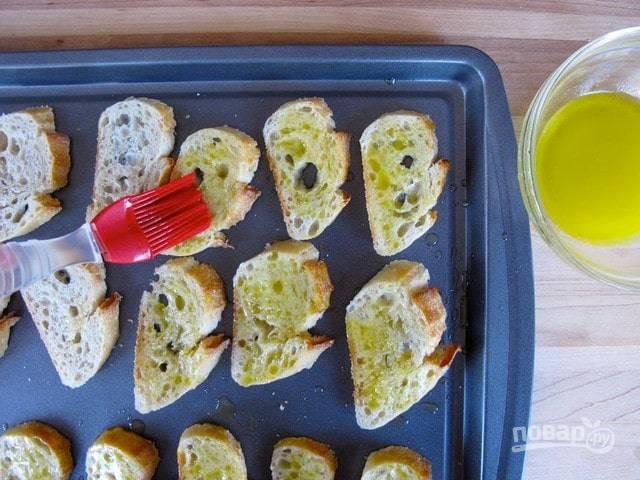 Растопите сливочное масло, а потом соедините его с оливковым. Смажьте смесью кусочки хлеба.