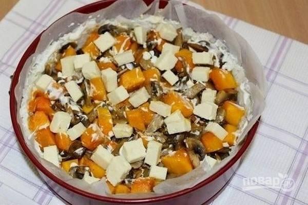 Через 20 минут смажьте бортики из риса сметаной, а на начинку положите кубики сыра и выпекайте пирог еще 10 минут.