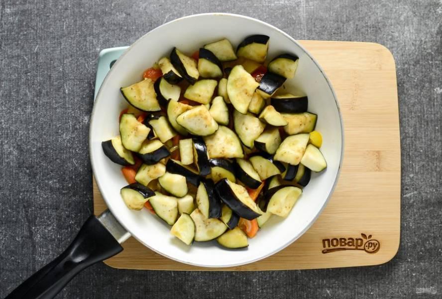 Баклажаны промойте в холодной воде и отожмите. Добавьте к остальным овощам. Перемешайте и жарьте на небольшом огне 5-7 минут.