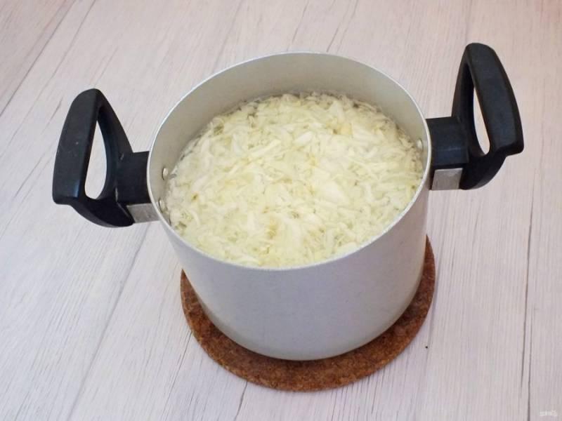 Налейте в кастрюлю 2 литра воды, доведите до кипения. Добавьте картофель и капусту. Варите на среднем огне в течение 15 минут.
