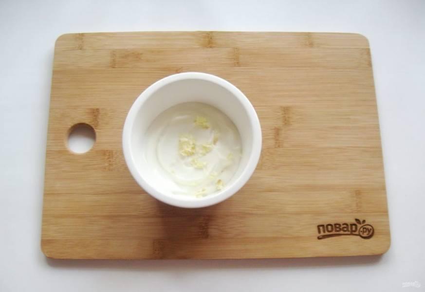В посуду для запекания выложить йогурт. Добавить соль, измельченный чеснок.