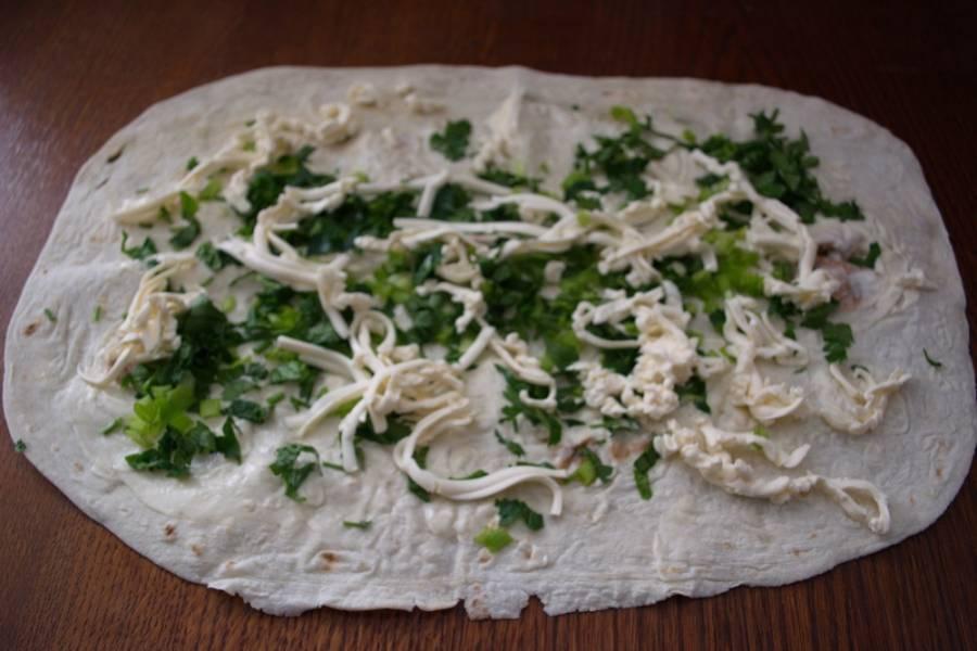 4. На крупной терке натрите плавленый сыр. Выложите на лаваш. Посолите и поперчите по вкусу.