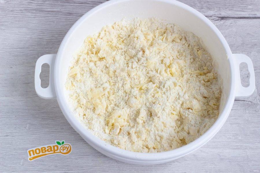 Добавьте кусочки холодного сливочного масла и руками разотрите всё в крошку.