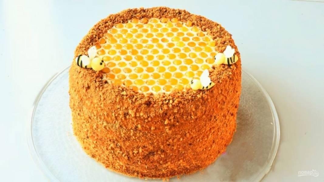 6. Переложите шоколад в виде сот на торт, украсьте медом, а бока обсыпьте крошкой из верхушек коржей. Отправьте торт в холодильник на ночь. Приятного аппетита!