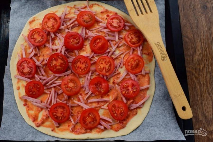 Распределите по всей лепешке половину начинки: колбасу, помидоры…