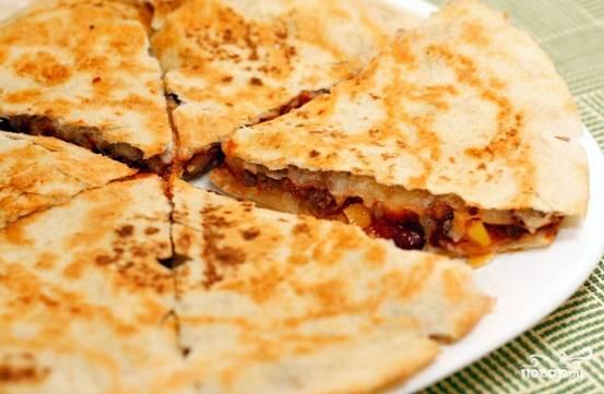 """6. Натрите сыр. Дно сковородки смажьте маслом. Положите тартилью. Сверху присыпьте ее сыром. Выложите фарш и распределите его. Фарш присыпьте сыром. Накройте второй тартильей. Обжарьте """"пирог"""" с обеих сторон до румяности. Кесадилья готова."""