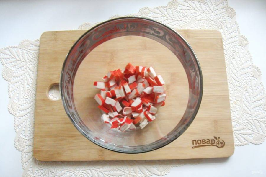 Крабовые палочки мелко нарежьте и выложите в салатник.