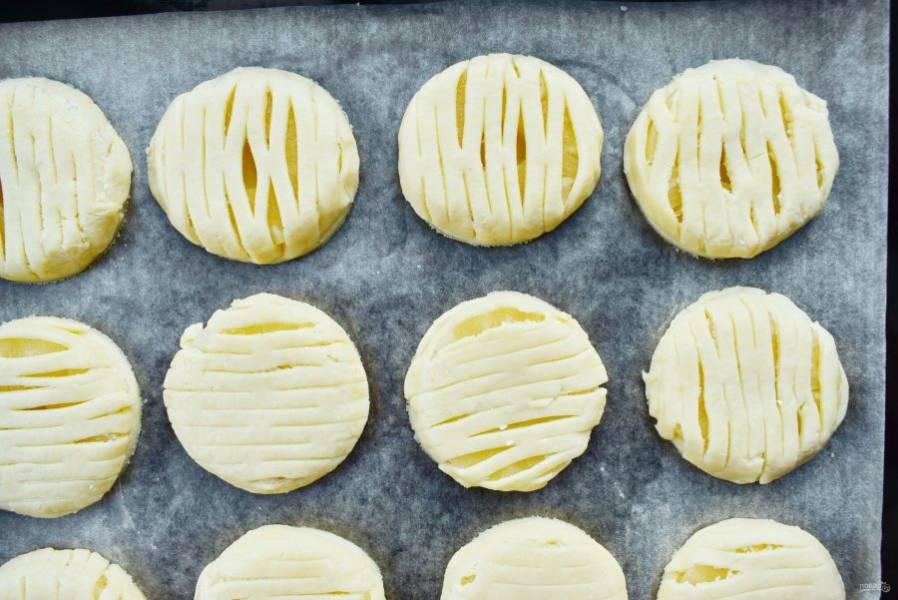 Раскатайте вторую часть теста, прокатайте специальным валиком и сделайте решетку. Вырубите кружки, разместите сверху ананасов, прижмите. Смажьте сверху слегка взбитым яйцом.