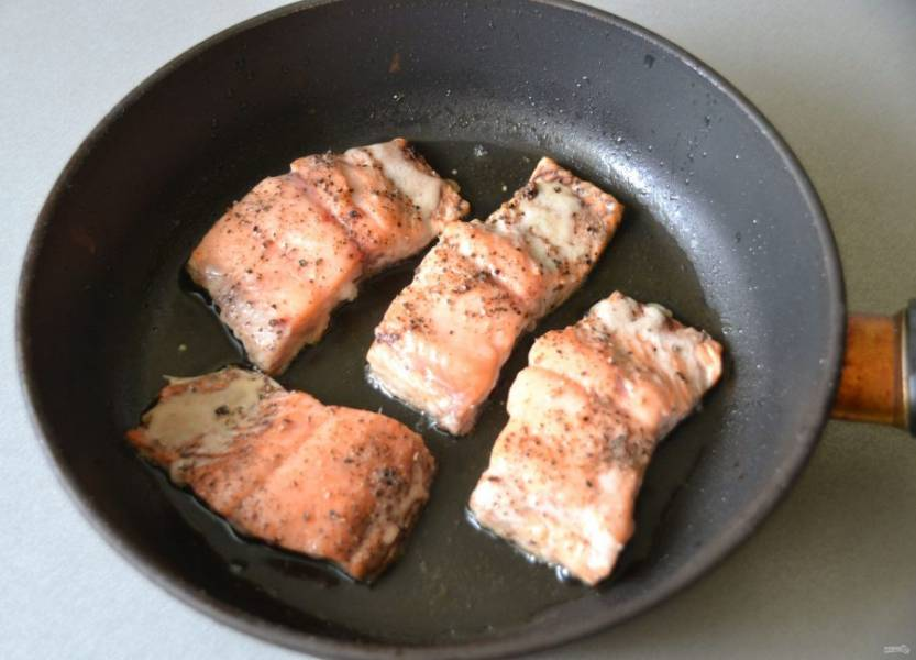 На разогретую сковороду налейте растительное масло и обжарьте лосось с одной стороны.