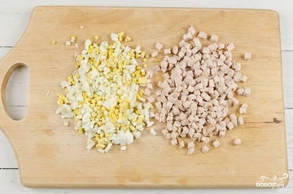 Яйца также отварите и охладите. Куриную грудку положите в кипящую воду на 20-25 минут. После приготовления - остудите. Порежьте яйца и курицу такими же кубиками, как и морковь с картофелем.