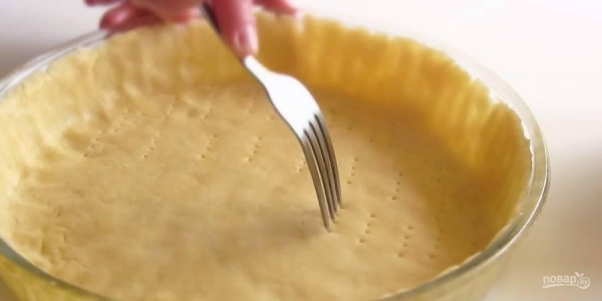 3. Приготовьте начинку: нарежьте большой пучок зеленого лука, яйца нарежьте кубиками и перемешайте. Тесто достаньте из холодильника, раскатайте в тонкий пласт и выложите в форму так, чтобы образовался бортик. Наколите тесто вилкой.