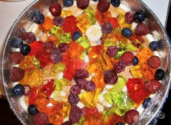4. Выкладываем фрукты, крекеры и ягоды, а также уже готовое желе, нарезанное кубиками, поверх основы торта. Заливаем всё сметанной смесью.