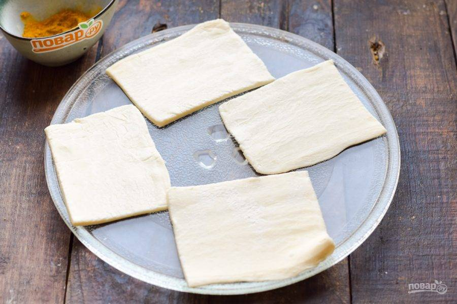 У меня было пресное слоеное тесто. Раскатайте тесто немного и разрежьте на 4 части. Переложите заготовки на стеклянную тарелку из микроволновой печи.