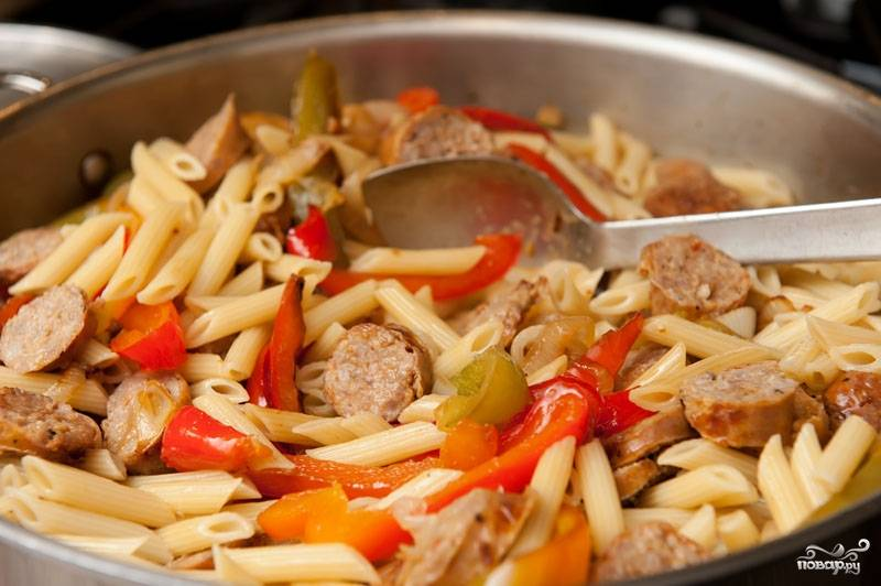 Когда макароны сварены, сливаем воду и добавляем к ним потушенные овощи и нарезанные сосиски, все перемешиваем на среднем огне. Если блюдо вам кажется суховатым, доливаем оливкового масла по вкусу.