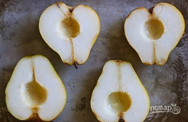 Груши хорошо вымойте, отрежьте хвостики и разрежьте фрукты на половинки, вычистив семена и сердцевинку. Выложите на противень. Включите духовку на 180 градусов.