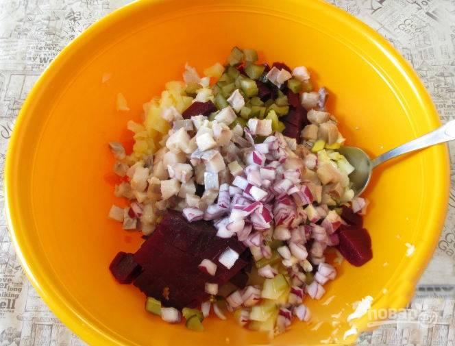 К нарезанным овощам добавьте также нарезанную кубиком сельдь.