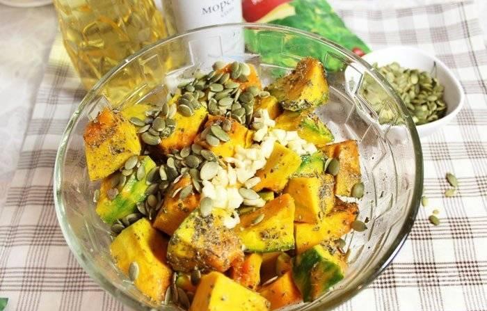 А кубики тыквы перемешайте с майораном, солью, маслом, очищенными семечками и мелко порубленным чесноком.