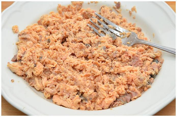 3. Размягчаем консервы вилкой, удаляя лишние косточки и хребты. Проводя постоянные эксперименты на кухне, я пришла к выводу, что для пирога лучше всего консервы из красной рыбы в собственном соку.