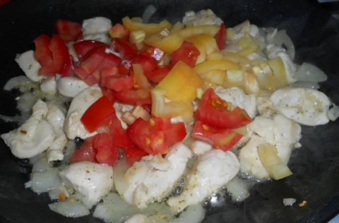 Перец и помидоры промываем, очищаем и нарезаем кубиками. Добавляем овощи на сковороду.