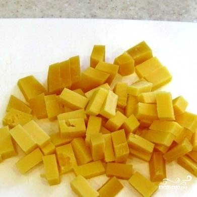 Кубиками аналогичного размера нарезаем сыр.