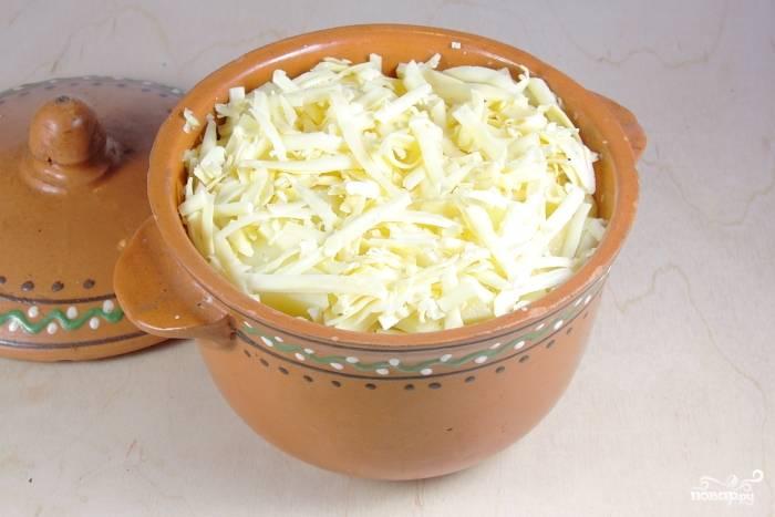 В горшочек сложить картофель, чеснок, посолить. Влить молоко и сверху засыпать тертый сыр.