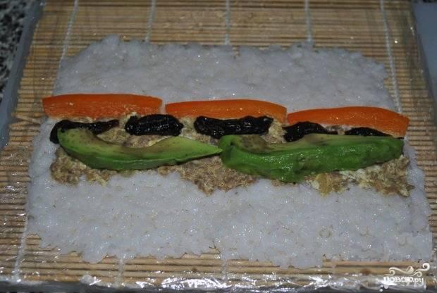 Авокадо, лук и огурец очистите и порежьте крупной соломкой. Тёплый рис заправьте уксусом с солью и сахаром, хорошо перемешайте. При помощи бамбукового коврика, покрытого пищевой плёнкой, сформируйте роллы, выложив слой риса, а затем фарш, овощи и чернослив.
