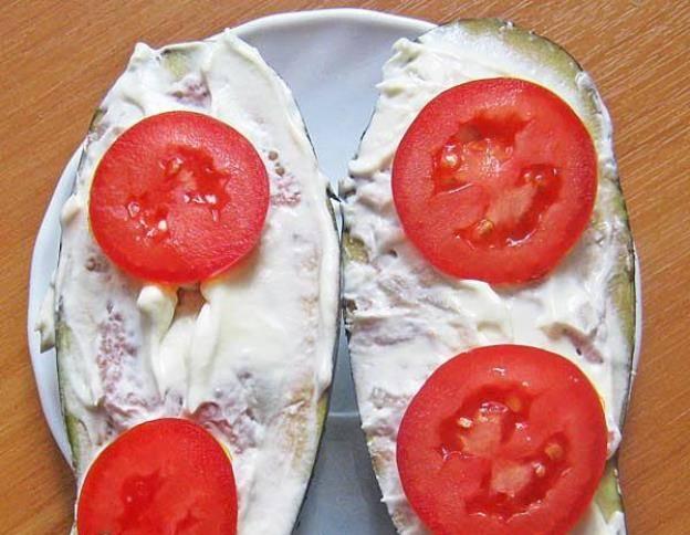 Сметану и майонез смешайте, при желании можно добавить мелко нарезанный чеснок. Получившимся соусом смажьте баклажаны. Украсьте порезанным кружочками помидором.