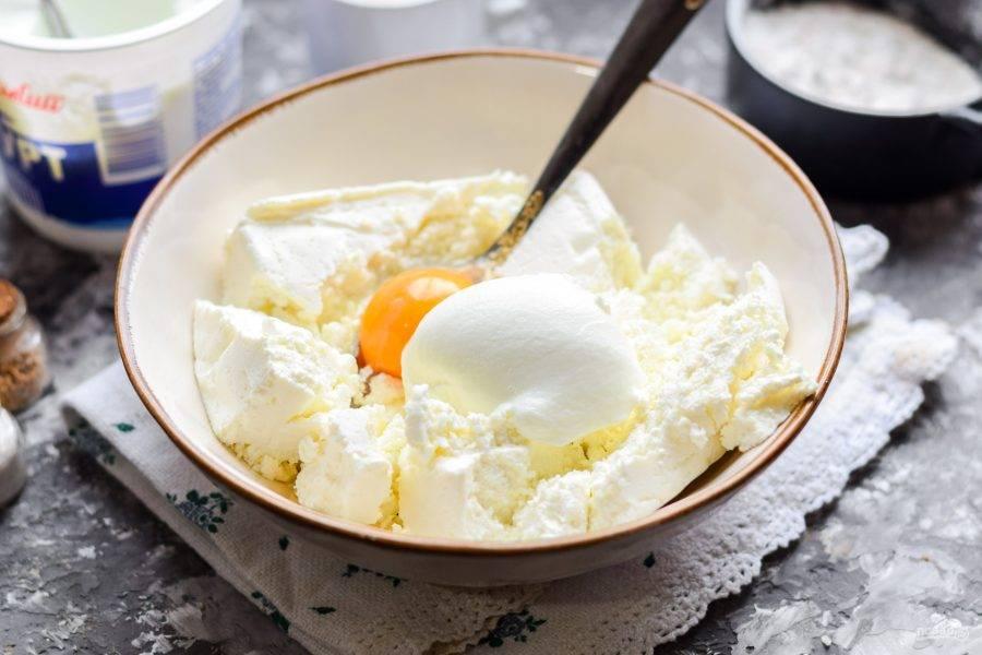 Творог переложите в миску, добавьте йогурт и куриное яйцо.
