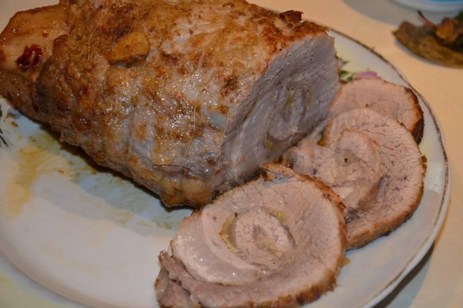 5. Когда мясо отварили, выключайте огонь и дайте ему еще постоять около часа. После этого можно вытаскивать, положить на блюдо и подождать, пока и рулета выйдет лишняя жидкость. Теперь нарезаем рулет из свинины вареный в домашних условиях, украшаем блюдо зеленью и подаем к столу (можно вместе с солениями или свежими овощами).