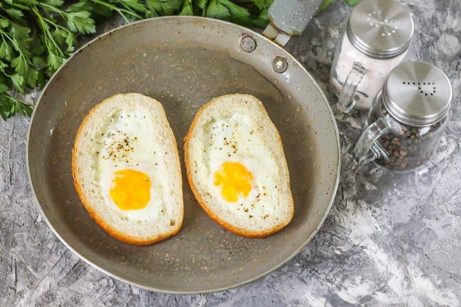 Жарьте яичницу в батоне не менее 3 минут на минимальном нагреве, иначе хлеб подгорит, а блюдо останется полусырым. Готовность яичницы определяется плотностью белков.