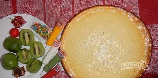 Начинку вылейте в заранее приготовленный корж и поставьте чизкейк в духовку, которую необходимо предварительно разогреть до 170 градусов. Выпекайте блюдо около часа. Готовый чизкейк украсьте дольками киви и любым другим декором на свое усмотрение.
