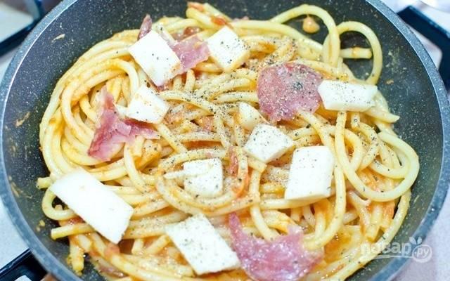 2.Взбейте яйца, добавьте тертый сыр и щепотку соли. Влейте взбитые яйца в макароны и хорошо перемешайте. На сковороде нагрейте оливковое масло, выложите половину спагетти, сверху положите мелкие кусочки копченого сыра, салями и немного молотого черного перца.