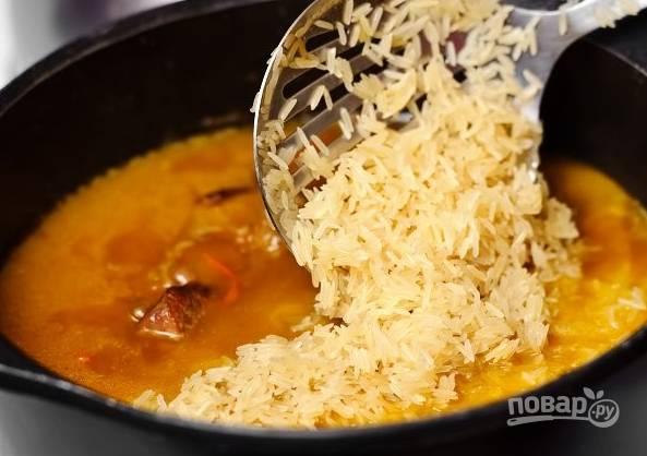 9. Через час аккуратно достаньте чеснок и выложите промытый рис.