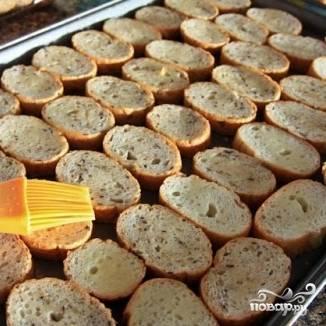 Выкладываем на противень ломтики белого хлеба. При желании их можно сверху смазать сливочным маслом, чтобы не было пригоревшей корочки.