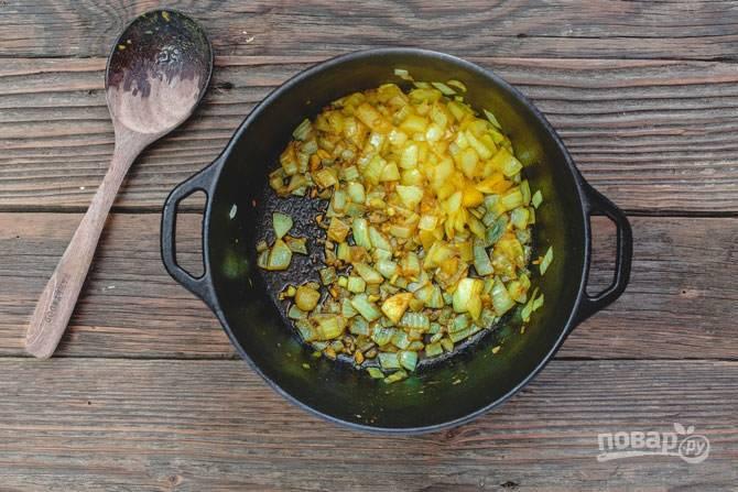 В большой чугунной кастрюле подогреваем оливковое масло, обжариваем рубленый лук, чеснок. Добавляем оставшиеся специи и хорошенько все перемешиваем. Тушим в течение 2-3 минут.
