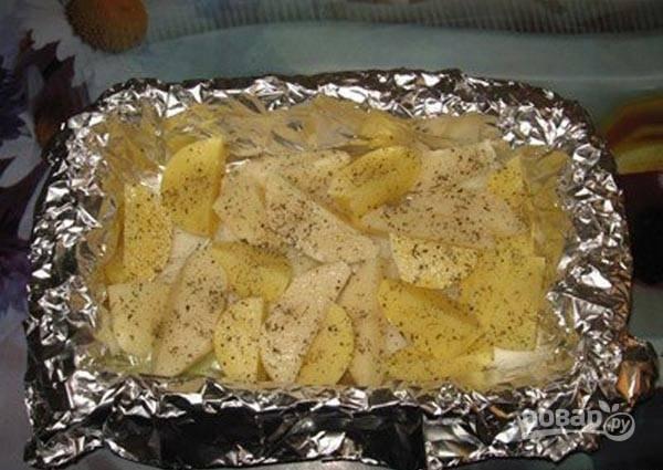 Затем нарежьте подготовленный картофель дольками. Выложите его на лук, добавив соль и специи.