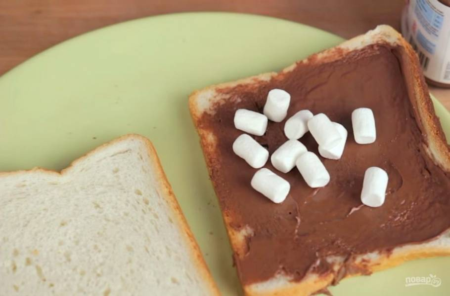 """1. Приготовить такие тосты невероятно легко. Для этого один ломтик хлеба смажьте """"Нутеллой"""" и выложите на него маршмеллоу однородным слоем."""