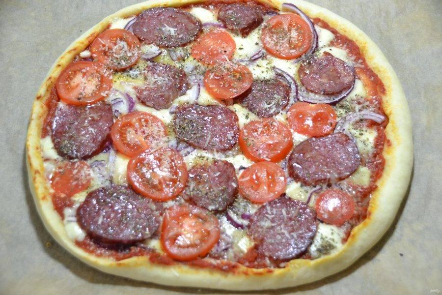 Выложите на пиццу салями, помидоры, присыпьте оставшимся пармезаном, сухим базиликом, сбрызните оливковым маслом и отправьте снова в духовку на 5-8 минут для окончательного запекания.