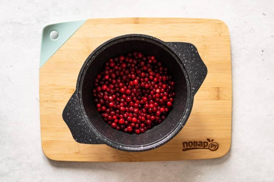 Бруснику помойте, переберите, если используете свежую ягоду. Переложите в кастрюлю с толстым дном. Добавьте воду и доведите до кипения.