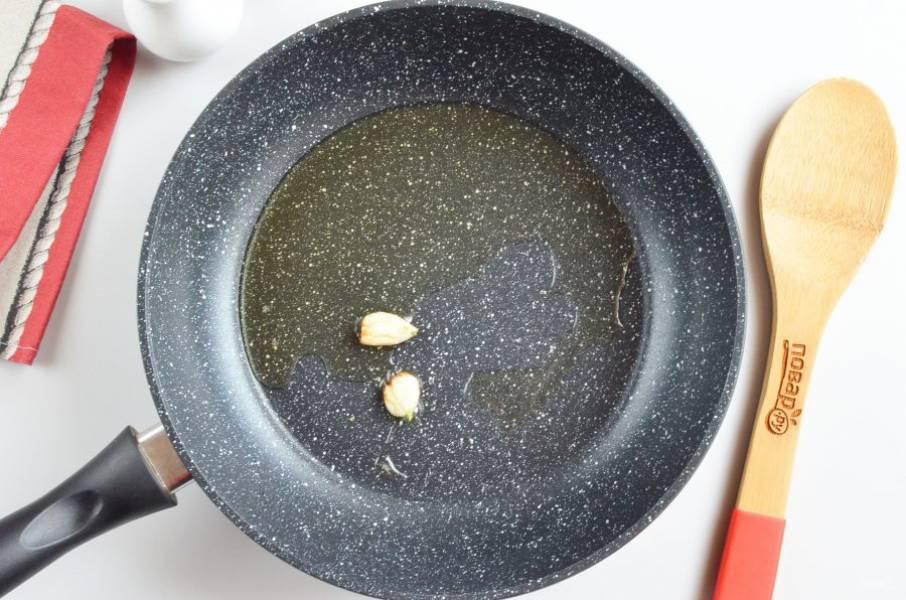 Разогрейте растительное масло, раздавите ножом чеснок и обжарьте в масле. После чего выбросите, чеснок нужен только для ароматизации масла.