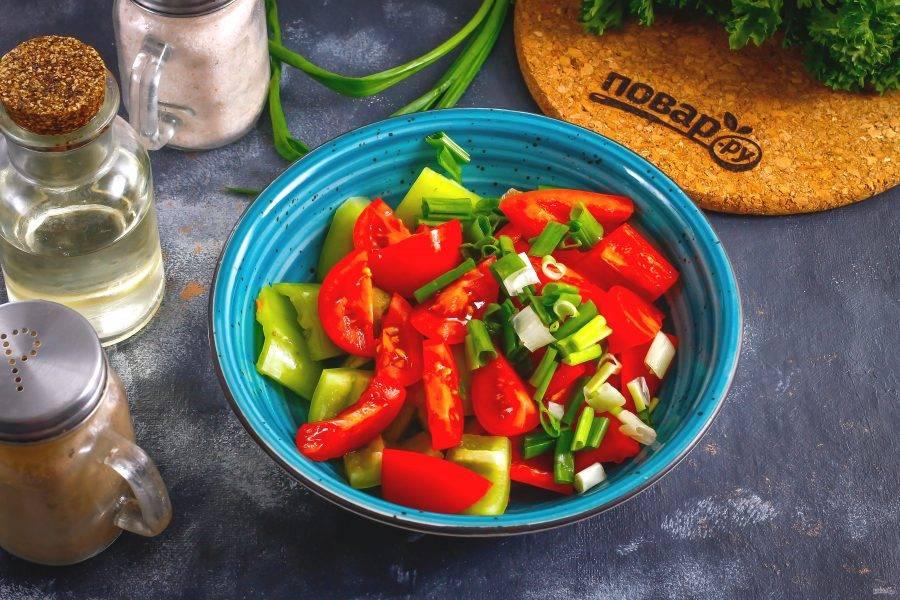 Пока обжаренные баклажаны остывают, промойте помидоры и зеленый лук. Нарежьте крупно и добавьте в емкость к болгарскому перцу.